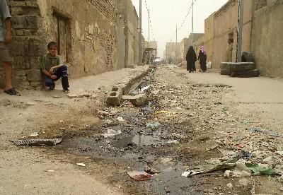 Un muchacho en cuclillas, junto al reguero de aguas residuales en una calle de Sadr City, Bagdad, 2006 (imagen procedente de faustablog.com).