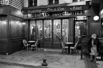 Dos mesas y unas cuantas sillas delante del bistrot (taberna) de la Rue de Lappe de París; y una mujer a la derecha (imagen procedente de borghesio.typepad.fr)