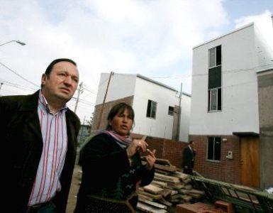 El presidente de La Rioja, Pedro Sanz, con Cecilia Castro, presidenta del Comité de Campamentos de Renca, visitando las nuevas viviendas de Renca, en las afueras de Santiago de Chile, en mayo de 2008 (imagen procedente de larioja.com).