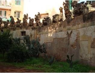 Figuras deformes en los muros de la Villa Palagonia, Bagheria, Sicilia. Detrás, construcciones banales, recientes; delante, algunos cactus. (Foto de 2007, procedente de socalgalopenwallet.blogspot.com).