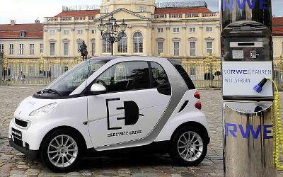 Un coche eléctrico y un poste de recarga (imagen procedente de autodescuento.com/blog)